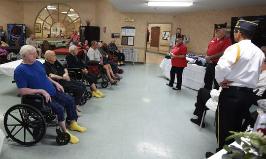 The row of veterans being honored Friday at Gassville Therapy & Living is welcomed by Linda Reed post adjutant of the Joe P. Joslin Jr. American Legion Post 23 in Cotter. The nine veterans assembled Friday were presented with U.S. flags and veterans quilts by U.S. Rep. Rick Crawford.