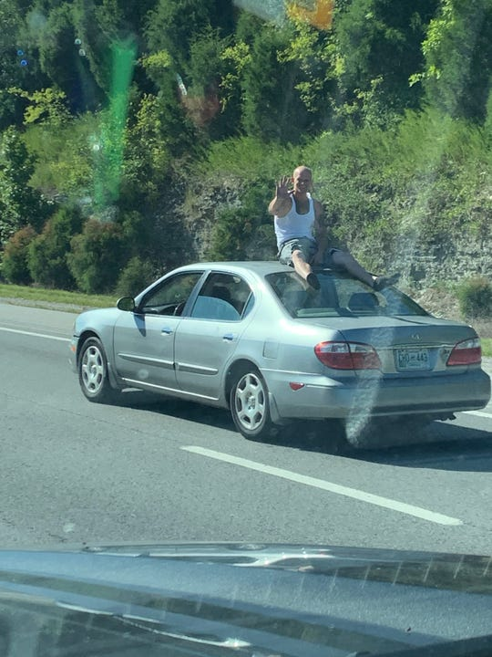 A man on top of a car traveling down Interstate 40 from Mt. Juliet to Nashville.