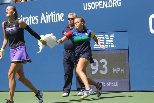 Petra Kvitová, of the Czech Republic, passes a towel back to Megan Cromie, 17, of Allendale, during day four of the US Open. Thursday, August 29, 2019
