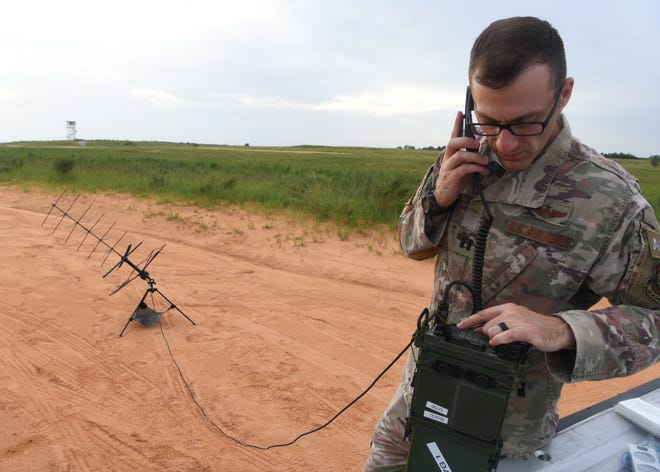 Air Force Capt. Peter Callo, a 621st Mobility Support Operations Squadron air mobility liaison officer from Joint Base McGuire-Dix-Lakehurst, N.J., inspects communications equipment during Battalion Mass Tactical Week at Fort Bragg, N.C., Aug. 20, 2019. Battalion Mass Tactical Week is a joint exercise involving the Air Force and Army designed to enhance service members' abilities by practicing contingency operations in a controlled environment.