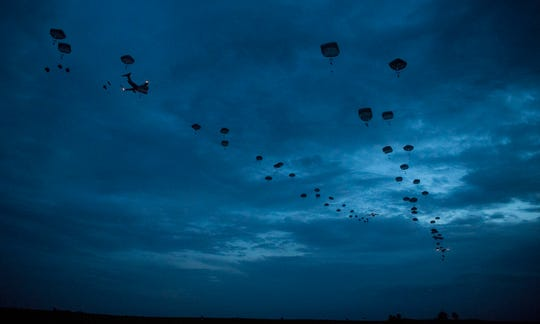 Air Force C-17 Globemaster IIIs and C-130J Super Hercules airdrop paratroopers onto a landing zone in low-light conditions during Battalion Mobility Tactical Week at Fort Bragg, N.C., Aug. 20, 2019. Battalion Mass Tactical Week is a joint exercise designed to enhance service members' abilities by practicing contingency operations in a controlled environment.