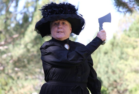 D'Ann Waters portrays Mattie Walling at an Aug. 30 dress rehearsal for Dining with the Dead at Greenlawn Cemetery in Farmington. Waters spoke about the time when a member of the Woman's Christian Temperance Union used a hatchet to break open a barrel of alcohol.