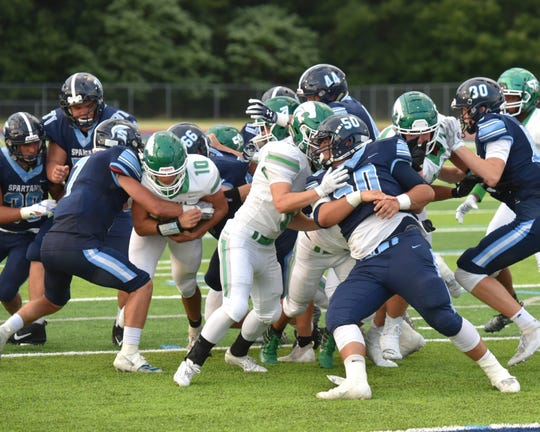 A lot of football players make contact in a near-goal-line situation as Novi's quartback Josh Erno (left) tries to gain some yardage.