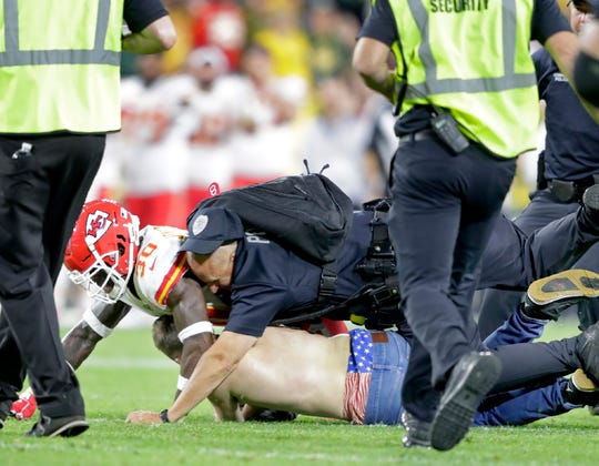 A fan is tackled after running onto the field during the Green Bay Packers preseason football game against the Kansas City Chiefs Thursday at Lambeau Field in Green Bay.
