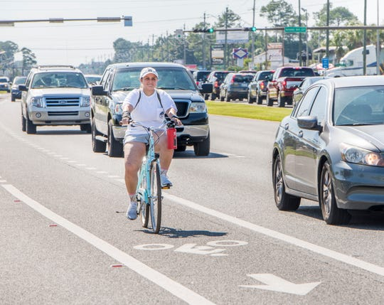 Veronica Vasquez rides her bike alongside the heavy traffic on U.S. 98 in Navarre on Friday.