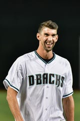 Michael Phelps reacts after throwing a ceremonial first pitch prior to the game between the Arizona Diamondbacks and the Colorado Rockies at Chase Field in August.