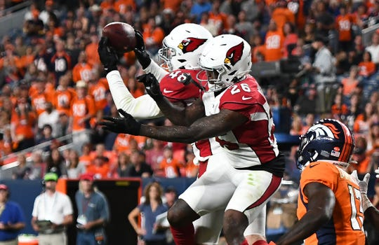 Aug 29, 2019; Denver, CO, USA; Arizona Cardinals linebacker Tanner Vallejo (48) and cornerback Brandon Williams (26) reach for the ball for a second quarter interception against the Denver Broncos at Broncos Stadium at Mile High.