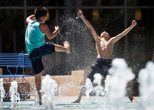 Drayden Gloria, de 9 años y de Phoenix (izq), patea agua a su hermano, Adriel, de 10 años, en el área de chapotederos de Cityscape en Phoenix, el martes 29 de mayo de 2018.