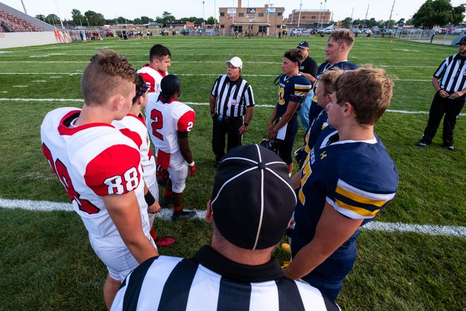 Players from Port Huron Northern and Lake Shore High School huddle before the coin toss Aug. 29, 2019, at Memorial Stadium in Port Huron.