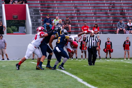 Lake Shore linebacker Brett Marks holds onto the football while being tackled by Port Huron Northern's Braiden McGregor (second from left) during their game Thursday, Aug. 29, 2019, at Memorial Stadium in Port Huron.
