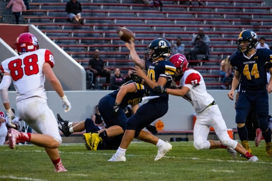 Port Huron Northern quarterback Seth Klink (10) throws the football as he gets tackled by Lake Shore's Benny Harr during their game Thursday, Aug. 29, 2019, at Memorial Stadium in Port Huron.