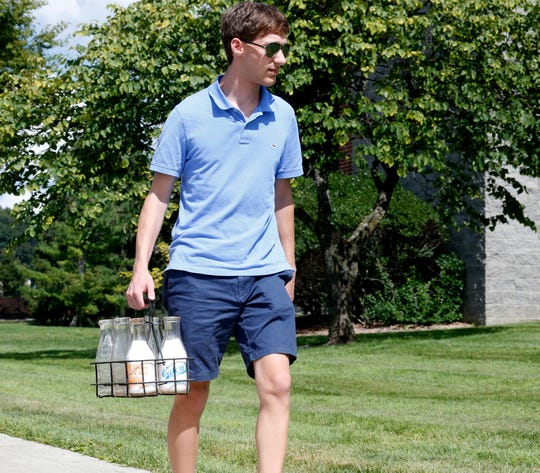 Alex Prizgintas carries a milk carrier with some of his vintage milk bottles at Marist College on August 29, 2019. Alex is the president of the Hudson Valley Bottle Club.