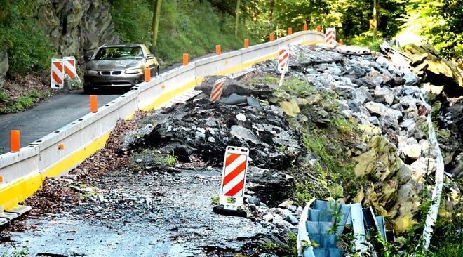 A vehicle uses a single available lane while passing destruction caused by flooding one year ago on Accomac Road Friday, Aug. 30, 2019. Bill Kalina photo