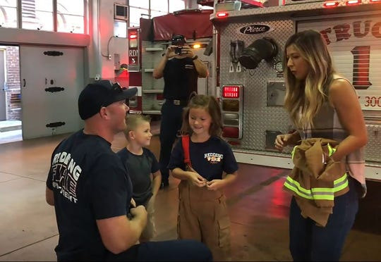 Redding firefighter Chris Frost (left) proposes to Tanja Moralli in front of her children Albert, 5, and Paisley, 7, on Sunday.