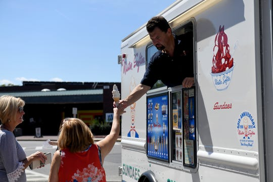 Anthony Sessa of Mister Softee hands a costumer a tall soft serve from his truck on Aug. 30, 2019. He plans to have his truck on the pad daily, living the legacy his dad and uncles started in Philadelphia in 1956., in Salisbury.