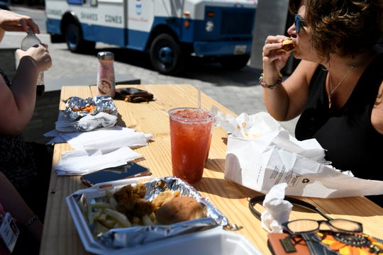 Robin Massey takes a bite of her food truck spoils as she spends her lunch away from PRMC at the Phase One Ribbon Cutting for Salisbury's downtown food truck pad on Friday, Aug. 30, 2019.