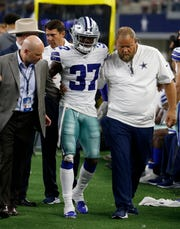 Dallas Cowboys defensive back Donovan Wilson (37) is assisted by team staff after suffering an injury in the second half of a preseason NFL football game against the Tampa Bay Buccaneers in Arlington, Texas, on Thursday.