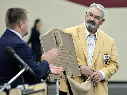 Royalton High School Principal Joel Swenson claps in this April, 2016, file photo as NFL Hall of Famer Jim Langer unveils a plaque that to be displayed in the school.