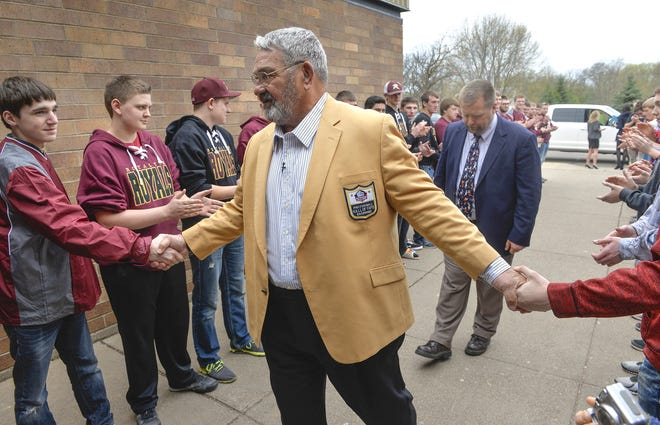 Royalton native NFL Hall of Famer Jim Langer shakes hands with members of the Royalton High School football team in April, 2016. He was on his way to a ceremony designating the school's Langer Field, named after him, as  an NFL Hometown Hall of Fame field.