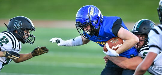 Cathedral's Maxwell Henke tries to avoid a tackle during the Thursday, Aug. 29, 2019, game against Spectrum at Husky Stadium in St. Cloud.