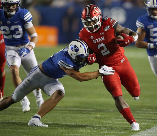 Utah running back Zack Moss, right, is tackled by BYU defensive back Austin Lee during the first half during an NCAA college football game Thursday, Aug. 29, 2019, in Provo, Utah. (AP Photo/George Frey)