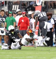 FAMU nickelback Terry Jefferson dives to tackle UCF running back Greg McCrae on Thursday, Aug. 29, 2019.