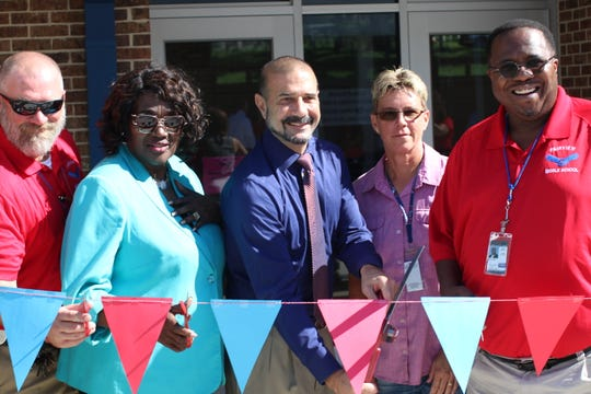Leon County Schools officials stand poised to cut the ribbon Friday morning at Fairview Middle School to celebrate the school's new main office and cafeteria buildings.