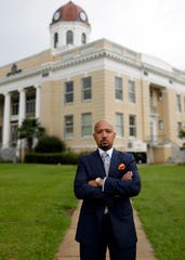 """Charles Gee stands in front of the Gadsden County Courthouse in his hometown, Quincy, which is also home to an office of his law practice, Gee & Lee Law. Gee was recently awarded the National Bar Association's Top 40 under 40 award and the group's most prestigious award """"Nation's Best Advocate."""""""