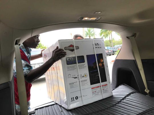 Victor Richard,left, helps Brian Ferguson load a generator into Ferguson's SUV Friday, Aug. 30. 2019, at the Lowe's store in Stuart