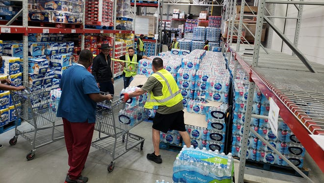 Sam's Club in Port St. Lucie employees assist customers by placing a limit of two cases of water into their shopping carts Friday morning.