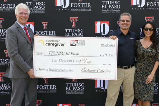 TTUHSC El Paso president and Paul L. Foster School of Medicine Dean Richard Lange, left, was presented Wednesday a $10,000 donation for medical students scholarships from Electronic Caregiver founder and CEO of Tony Dohrmann and his wife Ingrid Dohrmann.