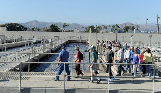 Eric Miller, front, lead operator for the Ventura Water Reclamation Facility, leads a tour along the facility's aeration tanks in Ventura.