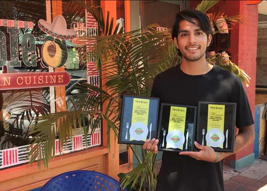 Marlon Herrera stands Friday outside El Guacamole on North High Street in Millville with three year's worth of awards for his family's Mexican cuisine restaurant.