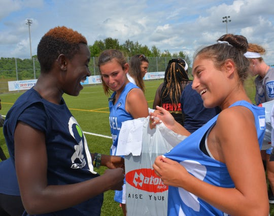 Ryan Lipton of New Rochelle and the Israeli team presents cleats to a Kenyan player during the U19 Women's Lacrosse World Championships in Aug. 2019. Lipton, who is shown showing the other player that they share the same No.12, has since become text-messaging friends with her.