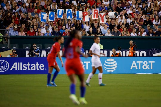 Fans hold up a sign for equal pay during the second half of an international friendly soccer match between the United States and Portugal, Thursday, Aug. 29, 2019, in Philadelphia. The United States won 4-0.