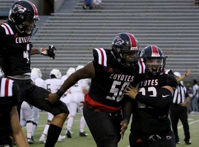Wichita Falls High's Marquis Smith (50) and Jacob Dollar (23) celebrate recovering a Chisholm Trail fumble Thursday, Aug. 29, 2019, at Memorial Stadium.