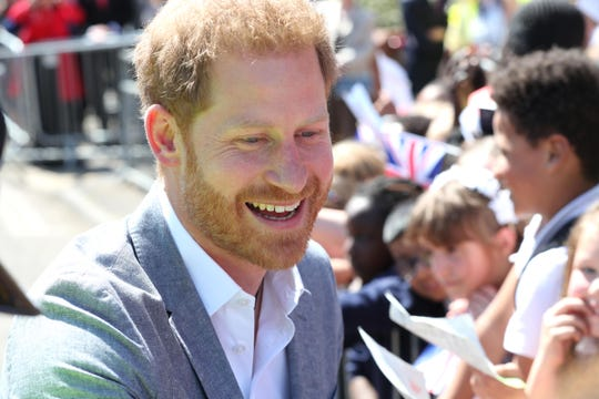 Prince Harry smiles at wellwishers as he arrives for a visit to the Barton Neighbourhood Centre on May 14, 2019 in Oxford, England.