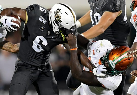 Central Florida receiver Marlon Williams (6) and Florida linebacker Nadarius Fagan (27) get a fist full of each other's facemask during the first half.