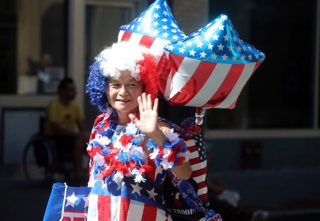 Annie Lin shows her American pride while marching in the annual Roanoke Labor Day Parade in downtown Roanoke, Va., on Saturday, Sept. 1, 2018. She passed out fortune cookies to the crowd with her son, Jerry Wu, not pictured.