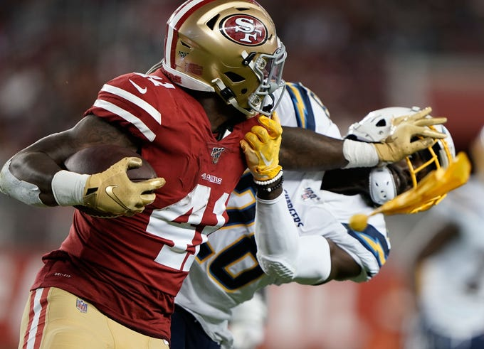 San Francisco 49ers running back Jeff Wilson (41) performs a stiff arm on Los Angeles Chargers defensive back Brandon Facyson (28) as a penalty flag is thrown during the second quarter at Levi's Stadium.