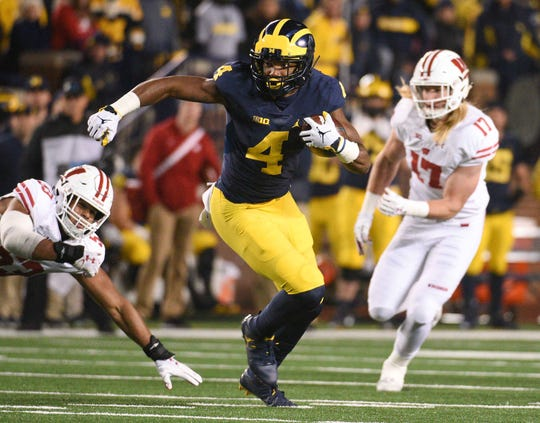Michigan wide receiver Nico Collins avoids Wisconsin defenders during their game in 2018.