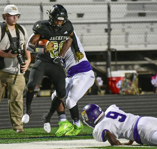 TL Hanna senior Ja'Nike Truesdale(20) runs out of bounds near Emerald freshman Kareem Goode(9) during the third quarter at T.L. Hanna High School in Anderson Friday, August 30, 2019.