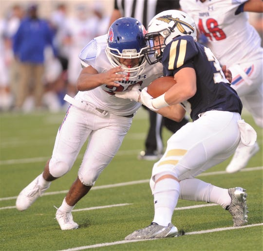 Cooper's Anthony Batrez, left, closes in on Keller running back Conner Medlock. Cooper beat the Indians 21-20 in the season opener Friday at the Keller ISD Athletic Complex in Keller.