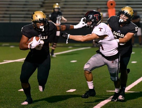 Abilene High running back Phonzo Dotson, left, tries to fend off Amarillo Tascosa's Kaden Thurman during the Eagles' season opener Aug. 30 at Shotwell Stadium.