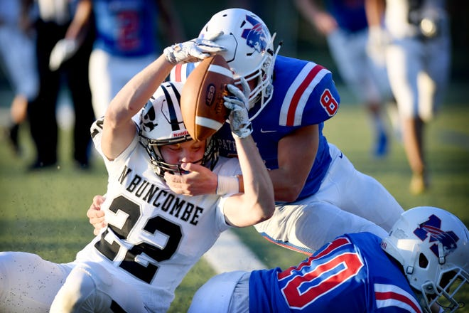 North Buncombe's Wesly Parran stretches for a touchdown as he is taken down by Madison's Clay Hilemon during their game at Madison High Schoo on Aug. 30, 2019.