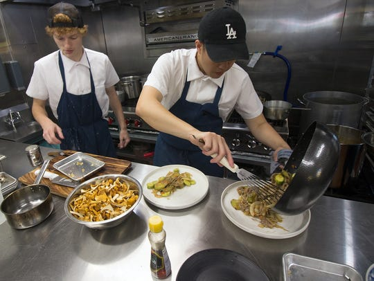 Chase Sturgeon, left, and Thai Nguyen work in the kitchen at Ba Sa Restaurant.