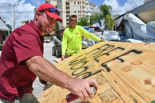 Nick Blazensky and Kevin Barfield of Barfield Contracting and Associates create a sign pointing the way to their location in Cocoa, Florida, Saturday afternoon, Aug 31, 2019. The building company provided free plywood and water at its office to anyone who needed it.