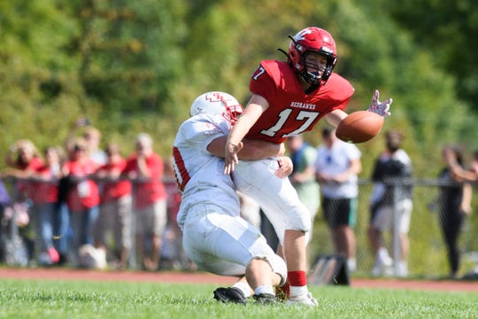 Rutland's Ethan Coarse (30) sacks CVU quarterback Jared Anderson's (17) and knocks the ball loose of during the high school football game between the Rutland Raiders and the Champlain Valley Union Redhawks at CVU High School on Saturday afternoon August 31, 2019 in Hinesburg, Vermont.