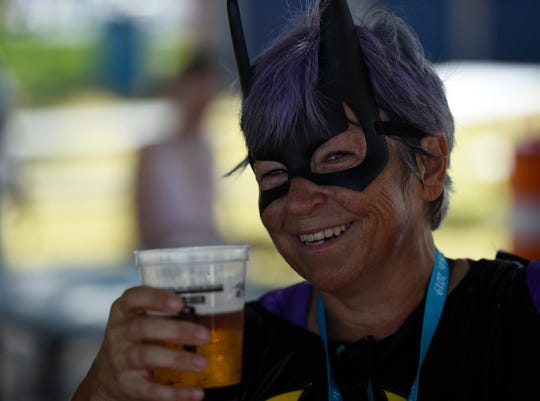 Debbie Parker holds a beer while dressed as Bat Girl at the third annual Arts Alive!, Saturday, Aug. 31, 2019, at the Arts Center of Corpus Christi. Parker ran in the 1/2K Beer Run.