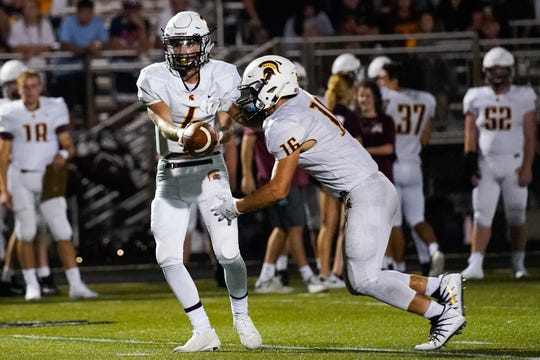 Turpin quarterback Justin Silverstein hands the ball off to running back Reece Evans during Friday night's matchup at Lakota East.
